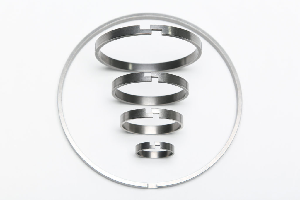 Step gap piston plunger wear rings for die casting machines