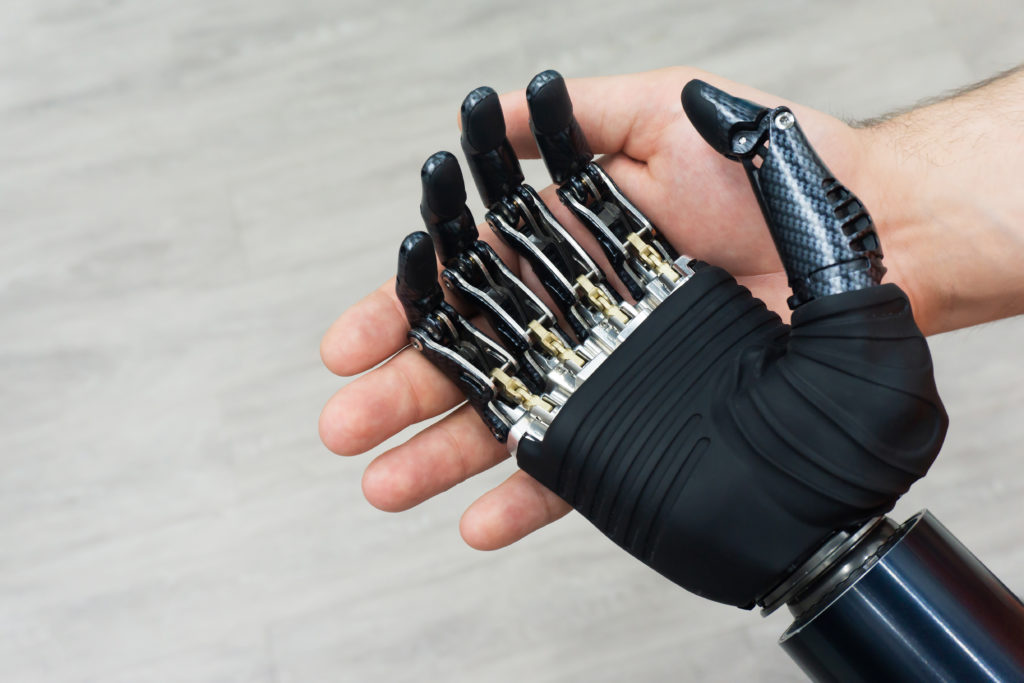 Male hand holding a robotic hand