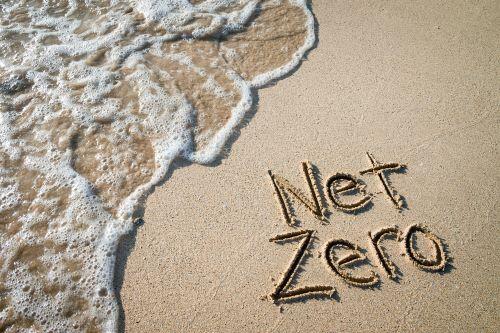 net zero handwritten on beach with oncoming wave