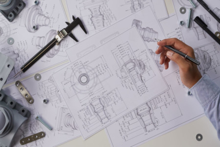 birds eye view of technical drawings laid out with vernier and various nuts and bolts on top